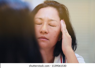 Image of elderly stressed woman in the mirror.She facepalm or cover her face by hand.4os Aain woman depressed,or may suffering from headaches and migraine as of Menopause or get trouble in her life.