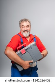 Image of an elderly worker in a blue combo box with a tool box