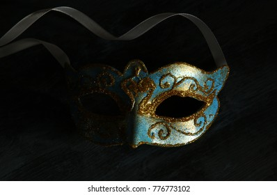 Image of elegant blue and gold venetian, mardi gras mask over dark background