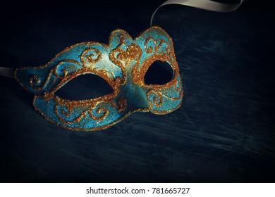 Image of elegant blue and gold venetian, mardi gras mask over black background