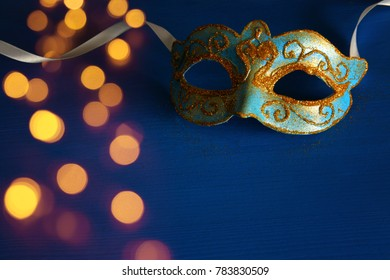 Image of elegant blue and gold venetian, mardi gras mask over blue background