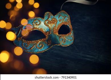Image of elegant blue and gold venetian, mardi gras mask over black background