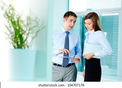 Image of elegant businessman explaining his plan to pretty colleague in office