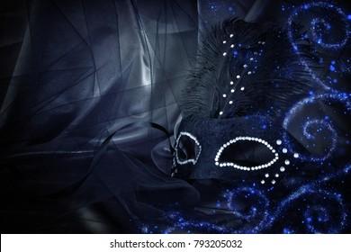 Image of elegant dramatic black venetian mask over tulle background
