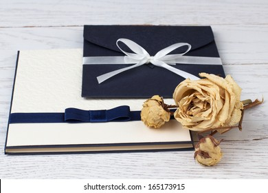 Image of an elegant envelope and an album on the table.