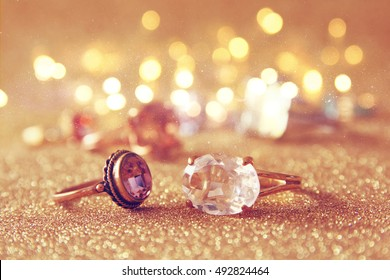 Image of elegant gold rings on gold glitter background