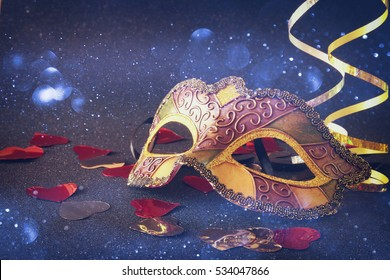 Image of elegant gold venetian, mardi gras mask on glitter background