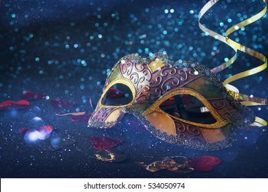 Image of elegant gold venetian, mardi gras mask on glitter background