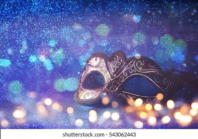 Image of elegant venetian mask on gold glitter background
