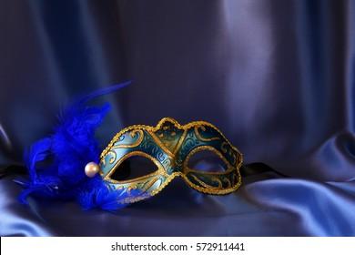 Image of elegant venetian mask on blue silk background