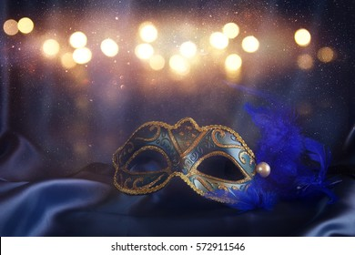 Image of elegant venetian mask on blue silk background