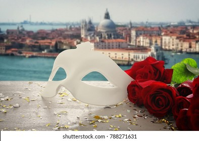 Image of elegant venetian mask and red roses over wooden table in front of blurry Venice background