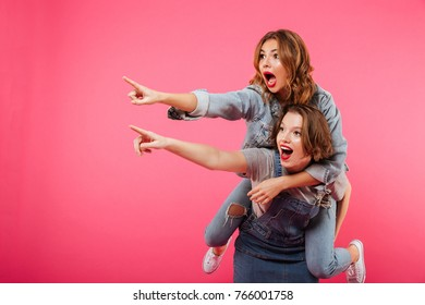 Image of emotional amazing two women friends have fun isolated over pink background. Looking aside pointing.