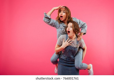 Image of emotional amazing two women friends have fun isolated over pink background. Looking aside.