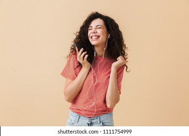 Image of emotional happy excited young curly woman listening music with earphones isolated over beige background dancing.