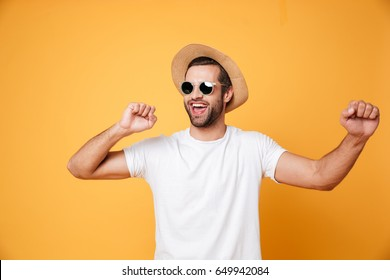 Image of emotional man in summer hat looking aside isolated dancing.