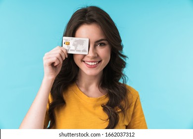 Image of emotional positive smiling young pretty woman posing isolated over blue wall background holding credit card covering eye.