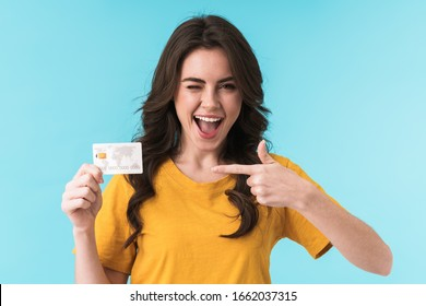 Image of emotional positive smiling young pretty woman posing isolated over blue wall background holding credit card pointing to card.