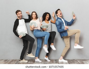 Image of emotionl excited group of friends standing isolated over grey wall background looking camera holding money make winner gesture.