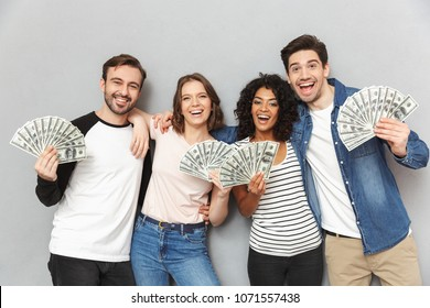 Image of emotionl excited group of friends standing isolated over grey wall background looking camera holding money.