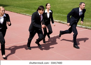 Image of employees running on sport track