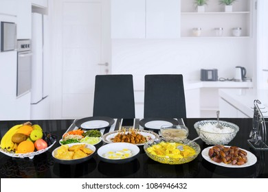 Image of empty two chairs with tasty meals served to break the fast. Shot in the kitchen