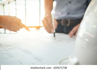 Image of engineer or architectural project, Close up of hands architects engineering working on blueprint with engineering equipment tool, blurred background.