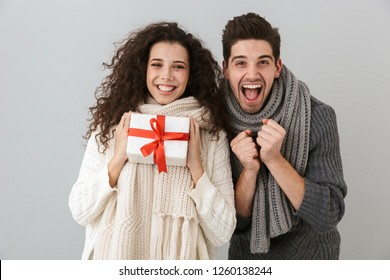Image of european man and woman rejoicing while standing with present box isolated over gray background