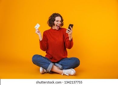Image of european woman 20s wearing sweater using cell phone and credit card while sitting on the floor isolated over yellow background