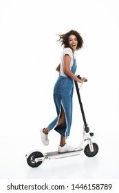 Image of excited african american woman dressed in denim overalls smiling at camera while riding on scooter isolated over white background