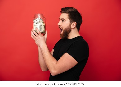 Image of excited bearded man standing isolated over red background wall holding jar full of money.