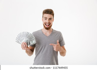 Image of excited cheerful young man standing isolated over white wall background holding money pointing.