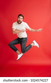 Image of excited emotional bearded man jumping isolated over red background wall pointing to copyspace.