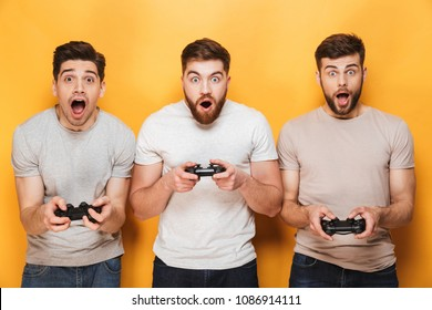 Image of excited emotional nervous young group of men friends standing isolated over yellow background play games with joysticks.