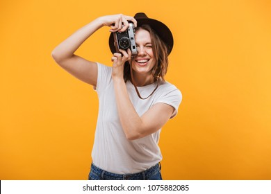 Image of excited emotional young woman photographer tourist standing isolated over yellow background holding camera.