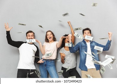Image of excited group of friends standing isolated over grey wall background over money.