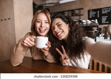 Image of excited happy pretty girls friends sitting in cafe take a selfie by camera.