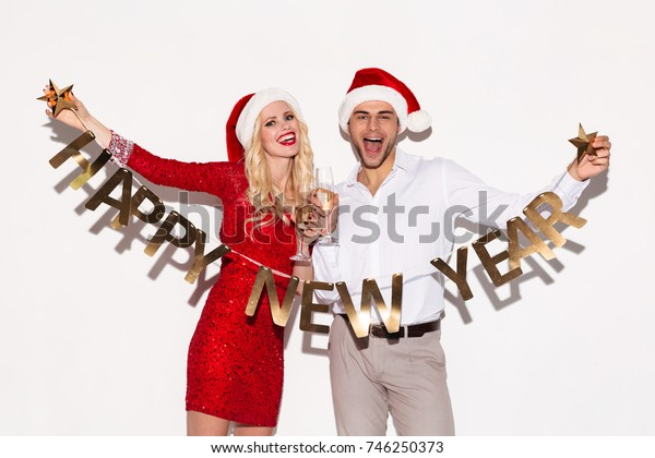 Image of excited happy young loving couple wearing christmas hats standing isolated over white background wall. Looking at camera drinking champagne holding happy new year garland.
