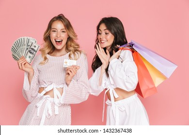 Image of excited happy young pretty women friends posing isolated over pink wall background holding shopping bags, credit card and money.