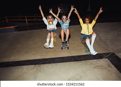 Image of excited multinational girls in streetwear smiling and riding on skateboards at night party outdoors