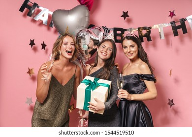 Image of excited party girls in fancy dresses celebrating birthday with gift box and champagne isolated over pink background
