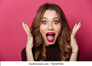 Image of excited screaming shocked beautiful woman standing isolated over pink background.