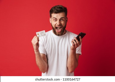 Image of excited screaming young man isolated over red wall background holding mobile phone and credit card. Looking camera.