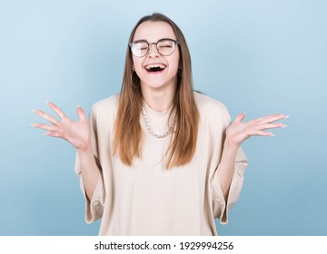 Image of excited screaming young woman wearing glasses standing isolated on blue background with closed eyes