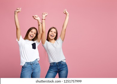 Image of excited two young twin sisters with beautiful smile posing with hands up over pink background.