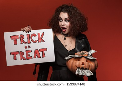 Image of excited witch girl holding halloween pumpkin and trick or treat board isolated over red wall