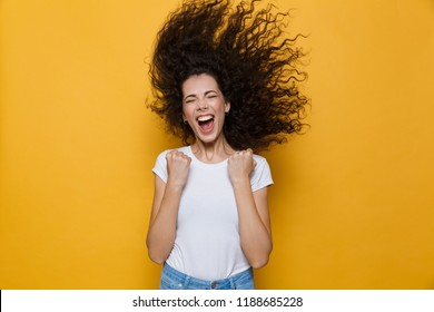 Image of excited woman with shaking hair screaming and rejoicing isolated over yellow background