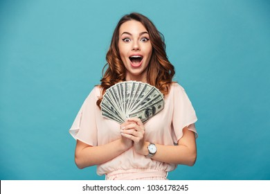 Image of excited young lady isolated over blue background. Looking camera showing money.