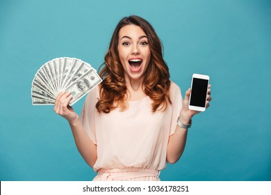 Image of excited young lady isolated over blue background. Looking camera showing display of mobile phone holding money.