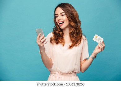Image of excited young lady isolated over blue background using mobile phone holding credit card.